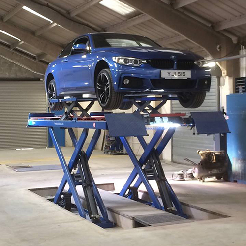 Blue BMW on scissor lift front view