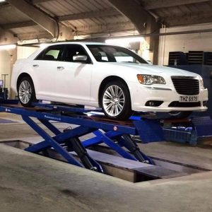 White car on scissor lift